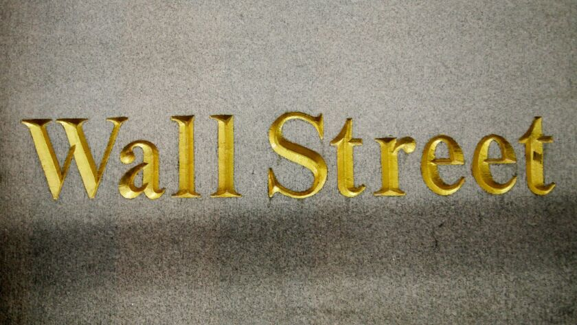 A Wall Street address is carved in the side of a building in New York.