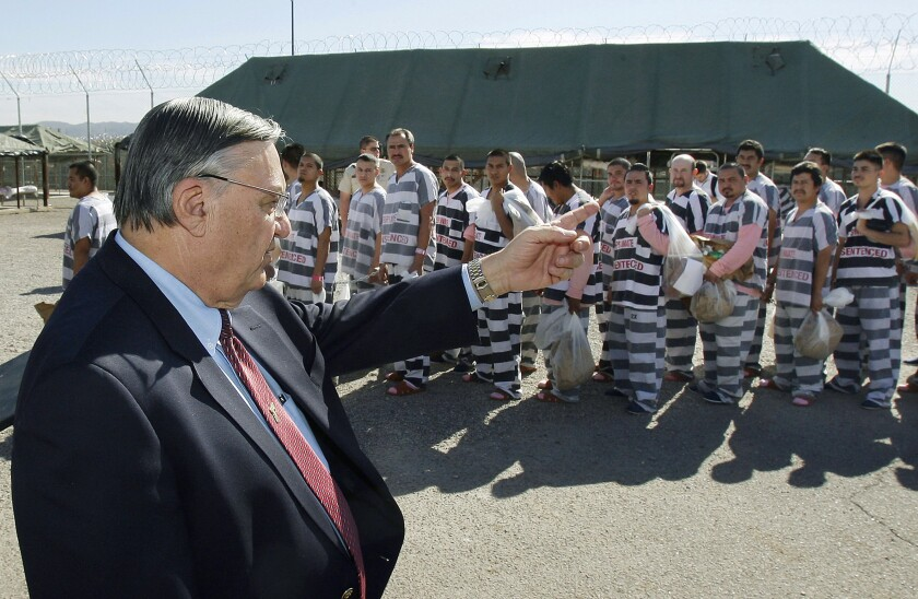 FILE - In this Feb. 4, 2009, file photo, Maricopa County Sheriff Joe Arpaio, left, orders approximately 200 convicted illegal immigrants handcuffed together and moved into a separate area of Tent City for incarceration until their sentences are served and they are deported to their home countries, in Phoenix. Arpaio, 87, is trying to regain his previous job as metro Phoenix's sheriff. The former lawman, who became a lightning rod for his hardline policies on illegal immigration, doesn't need the money and denies he's running to stroke his ego or garner publicity. Instead, he says he wants to do whatever he can to support President Donald Trump and vows to bring back his immigration crackdowns and jail tents. (AP Photo/Ross D. Franklin, File)