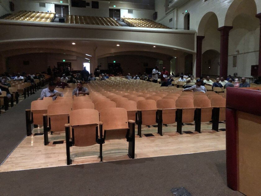City Section football coaches sit in the Fairfax High auditorium, with many empty seats, for a meeting.