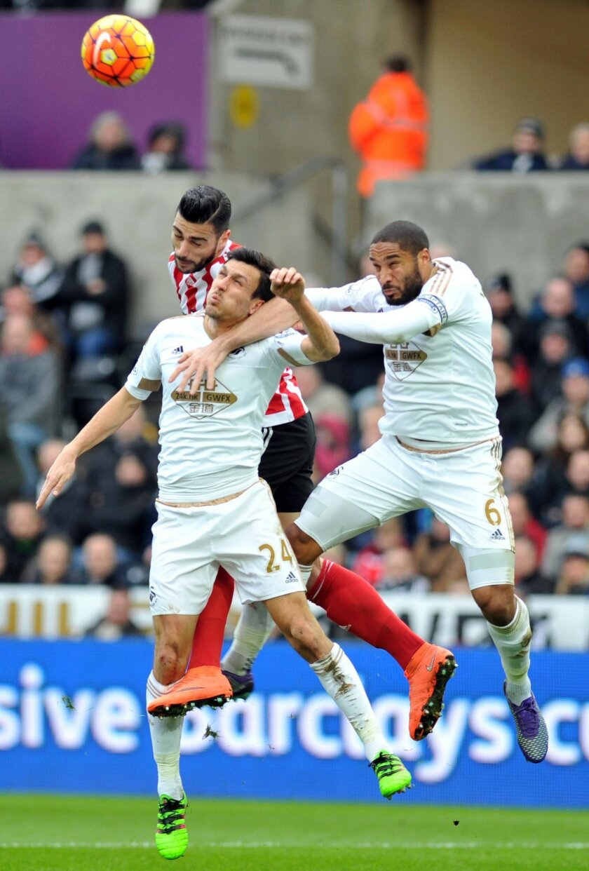 Southampton's Graziano Pelle, left, battles for the ball with Swansea City's Jack Cork and Ashley Williams, right, during the English Premier League soccer match at the Liberty Stadium, Swansea, Wales, Saturday Feb. 13, 2016. (Simon Galloway/PA via AP) UNITED KINGDOM OUT