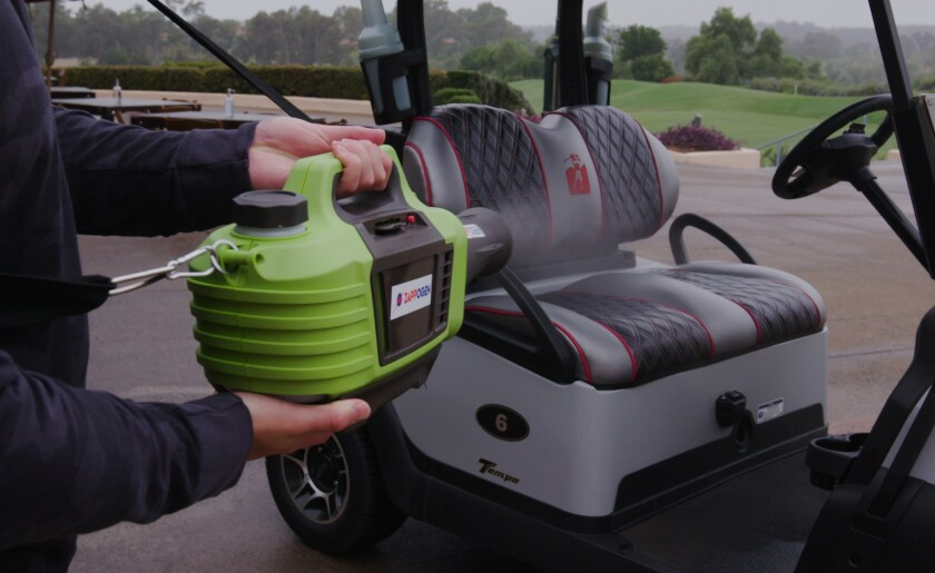 The Zappogen electro-sprayer works to disinfect a golf cart.