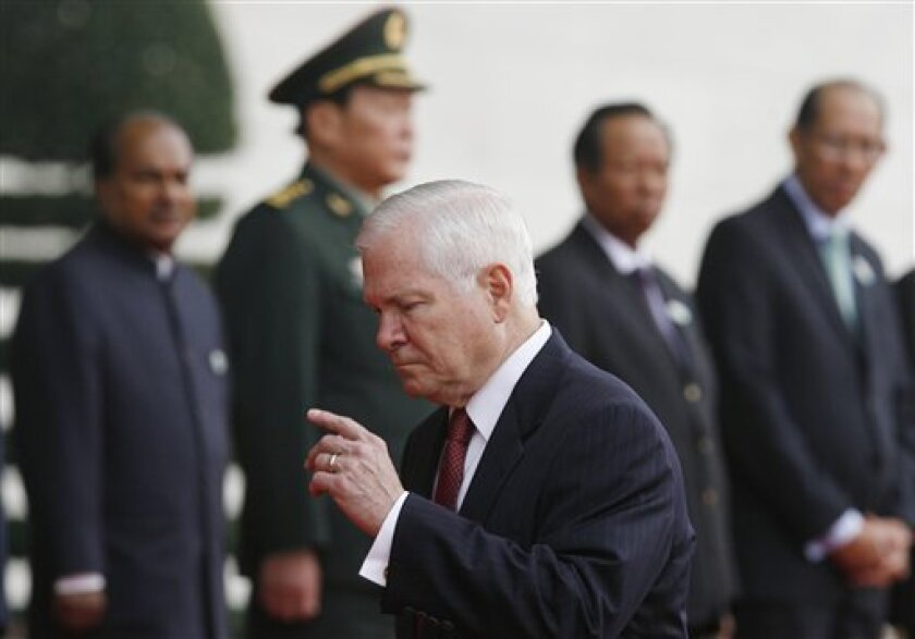 FILE - In this Oct. 12, 2010, file photo U.S. Defense Secretary Robert Gates gestures as he walks past, from left, India's Defense Minister Shri AK Antony, China's Defense Minister Liang Guanglie, Cambodia's Defense Minister Tea Banh and Brunei's Deputy Defense Minister Mustappa Sirat on occasion of the first Association of Southeast Asian Nations (ASEAN) Defense Ministers Meeting Plus in Hanoi, Vietnam. After a rocky year for U.S.-Chinese relations and in hopes of strengthening relations with the rising military power and global competitor Gates is set to depart Saturday, Jan. 8, 2011, on an Asia trip to meet with Chinese President Hu Jintao a week ahead of Hu's planned state visit to Washington. (AP Photo/Kham, Pool, File)