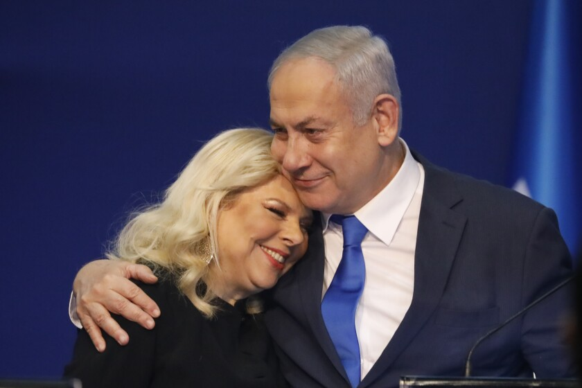 Prime Minister Benjamin Netanyahu hugs wife Sara after exit poll results in Tel Aviv.