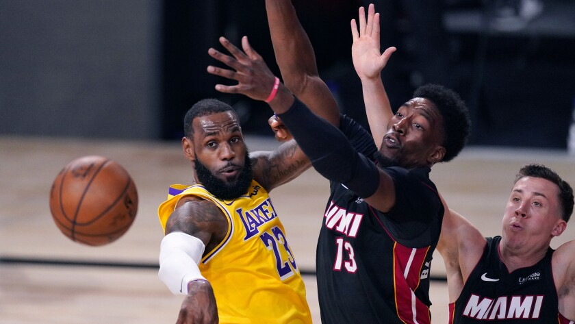 Lakers forward LeBron James passes the ball after being met at the basket by Heat center Bam Adebayo during Game 1..