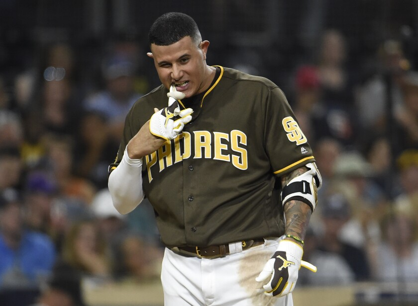 Manny Machado pulls off his glove with his teeth after striking out during the fifth inning of the Padres game against the Rockies on Friday night at Petco Park.