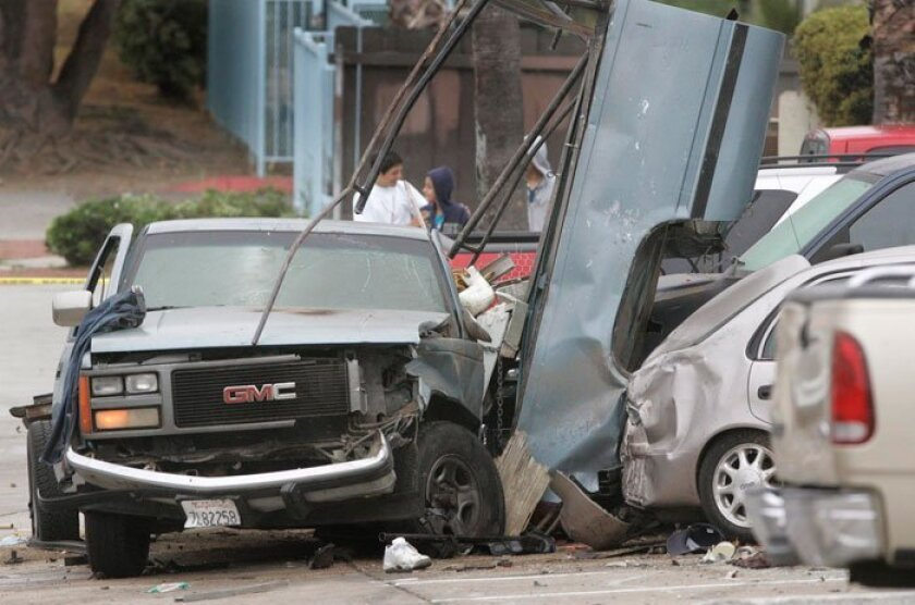 A pickup truck that struck a San Diego police patrol car sits with its bed sandwiched against one of the vehicles it later struck on Altadena Avenue early Thursday, June 20, 2010.