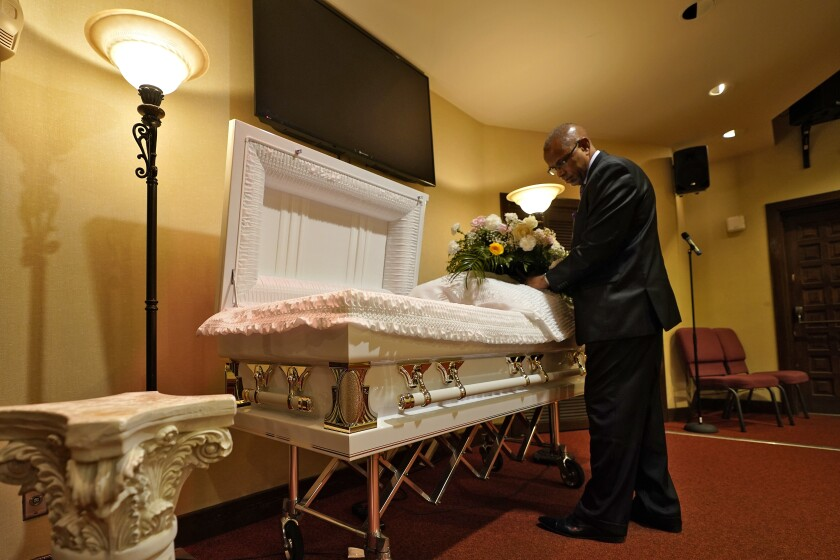 FILE - In this Thursday, Sept. 2, 2021 file photo, a funeral director arranges flowers on a casket before a service in Tampa, Fla. According to a study published Thursday, Oct. 7, 2021, by the medical journal Pediatrics, the number of U.S. children orphaned during the COVID-19 pandemic may be larger than previously estimated, and the toll has been far greater among Black and Hispanic Americans. (AP Photo/Chris O'Meara, File)