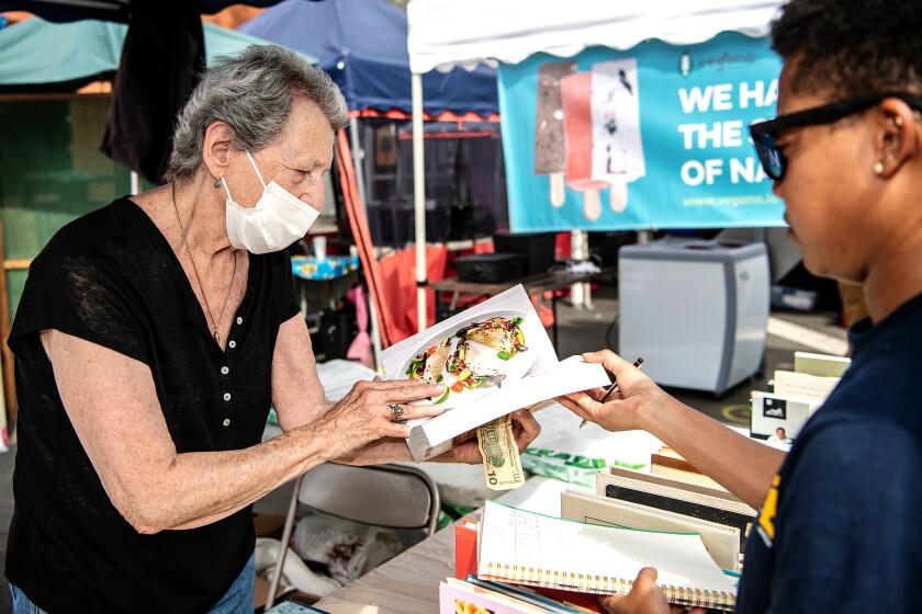A woman holding a $10 bill flips through a cookbook as a man looks on.