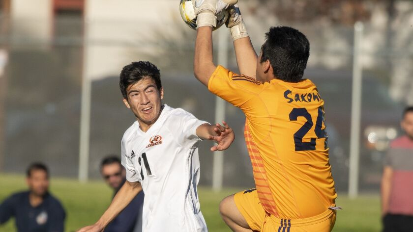 Los Amigos' Francisco Lopez goes up for a ball against Loara's goal keeper Luis Garcia during a Gard