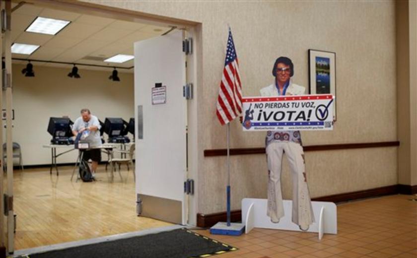 Esta foto de archivo muestra un letrero en español, con la figura de un imitador de Elvis Presley, que anima a la gente a que vote en un recinto electoral antes del día de la elección primaria, en Las Vegas. (AP Foto/John Locher, archivo)