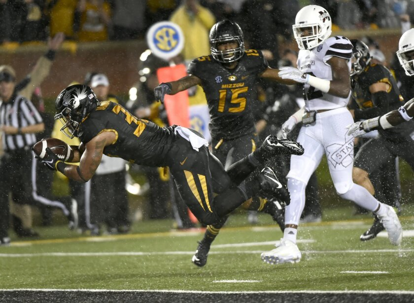Missouri running back Russell Hansbrough, left, dives into the end zone for a touchdown past teammate linebacker Grant Jones, center, and Mississippi State defensive back Jamal Peters, right, during the first half of an NCAA college football game on Thursday, Nov. 5, 2015, in Columbia, Mo. (AP Phot
