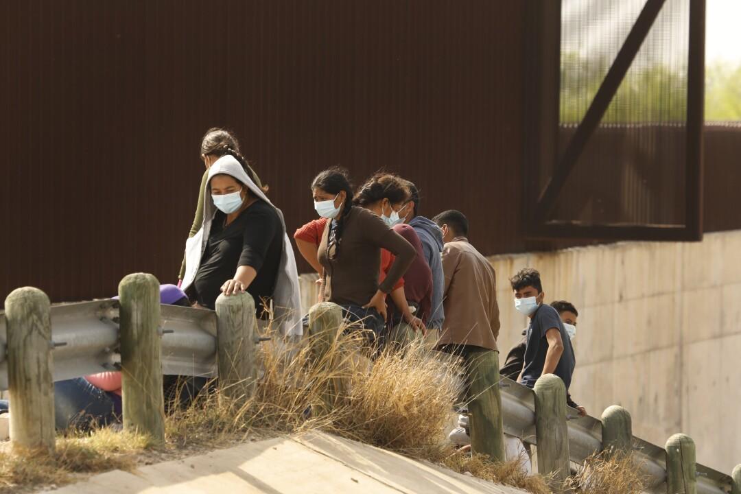 Asylum seekers sit on a metal guardrail alongside a barrier