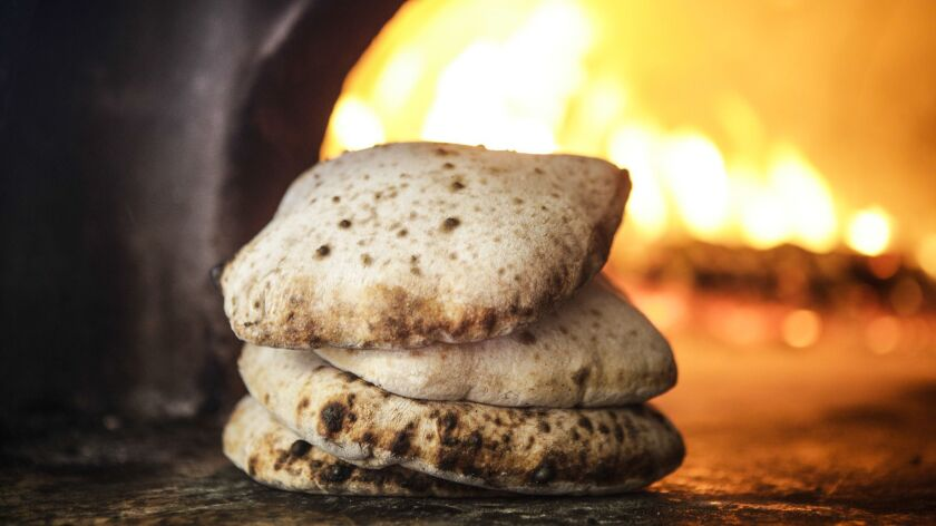The pita flatbread puffs up in the fire oven and bakes very quickly.
