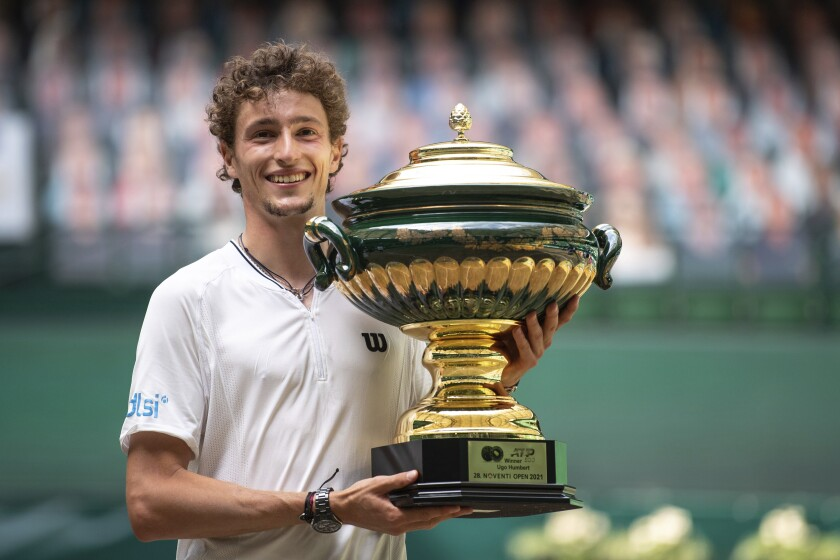 Ugo Humbert of France celebrates with the trophy after winning the final of the ATP tennis tournament in Halle, Germany, Sunday, June 20, 2021. (Marius Becker/dpa via AP)