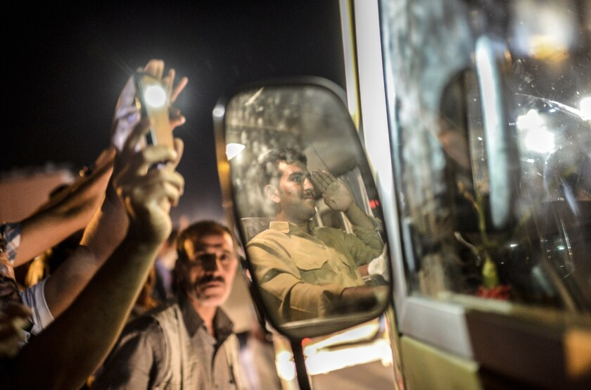 Kurds in Viransehir, Turkey, wave as a peshmerga fighter headed for the Syrian border town of Kobani salutes on Oct. 29.