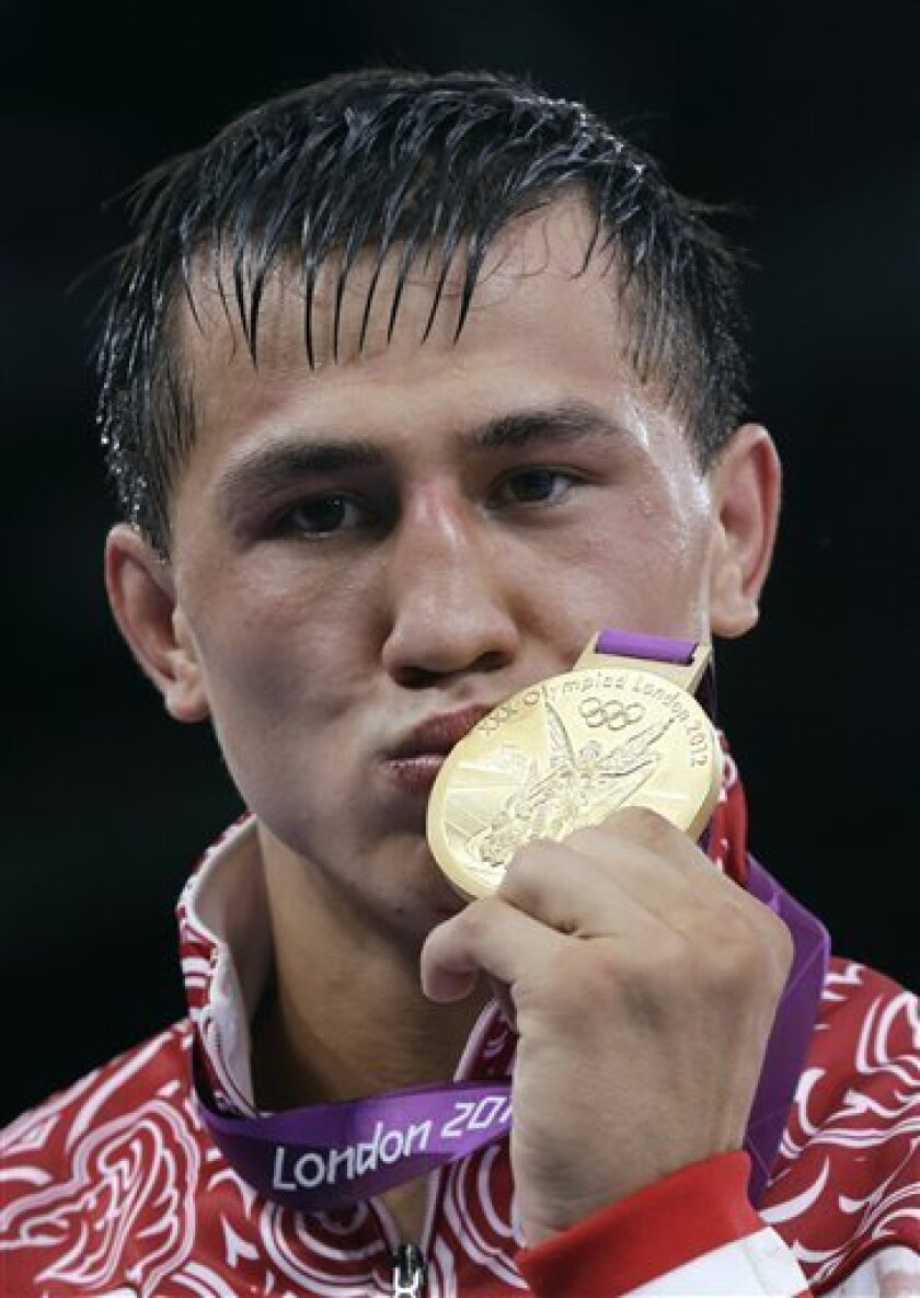 Russia's Roman Vlasov kisses his medal on the podium after winning the 74-kg Greco-Roman wrestling gold medal match at the 2012 Summer Olympics, Sunday, Aug. 5, 2012, in London. (AP Photo/Paul Sancya)