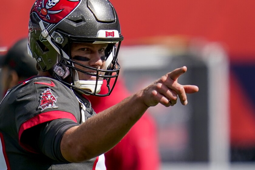 Buccaneers quarterback Tom Brady points at a teammate while directing the offense.
