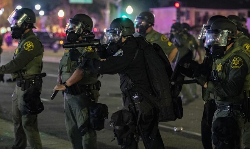 Un oficial de policía de Santa Ana dispara gases lacrimógenos contra una multitud durante una protesta, el sábado.