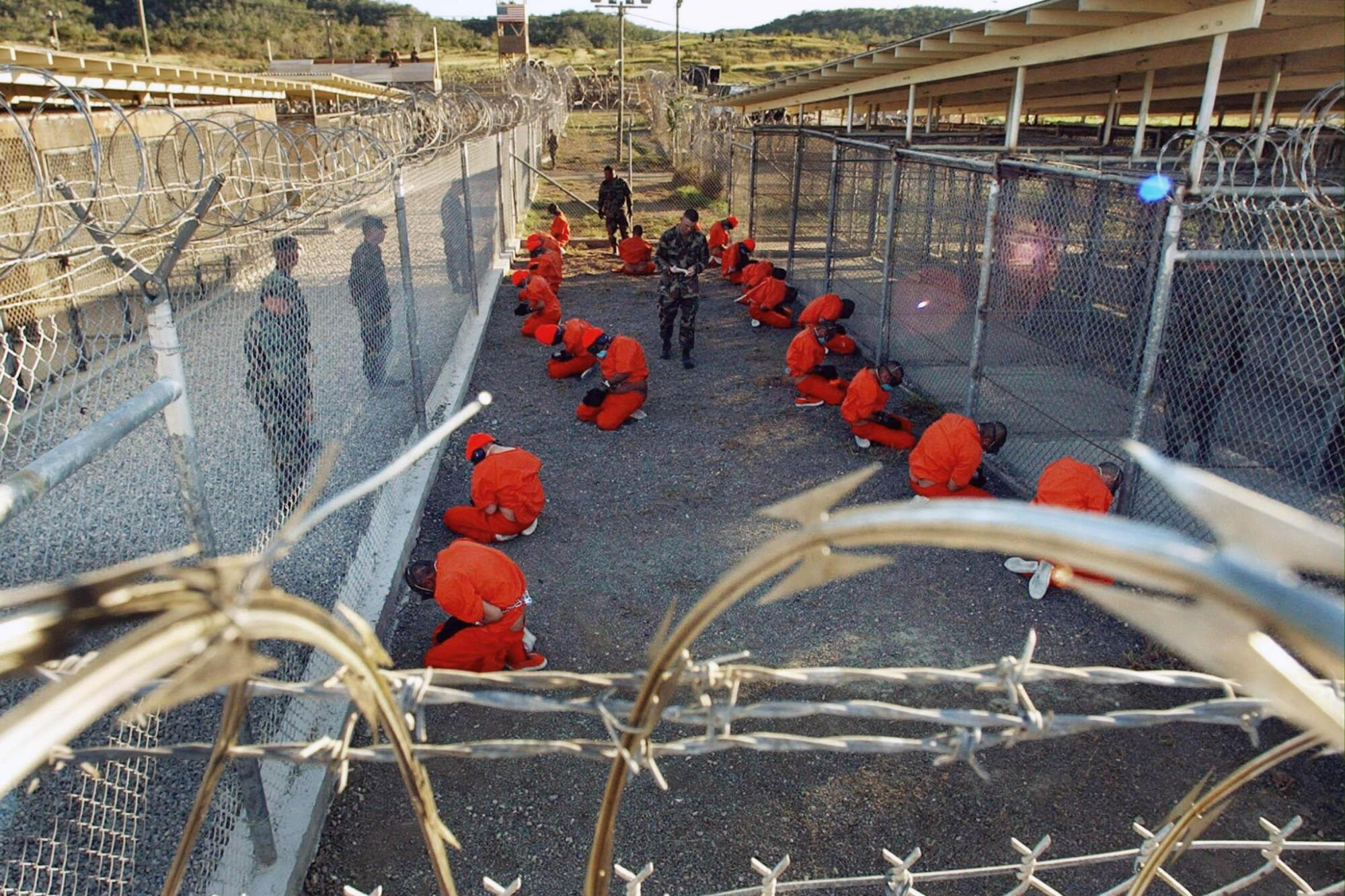 Two rows of men in orange jumpsuits sit in a fenced-off area, watched by men in military fatigues
