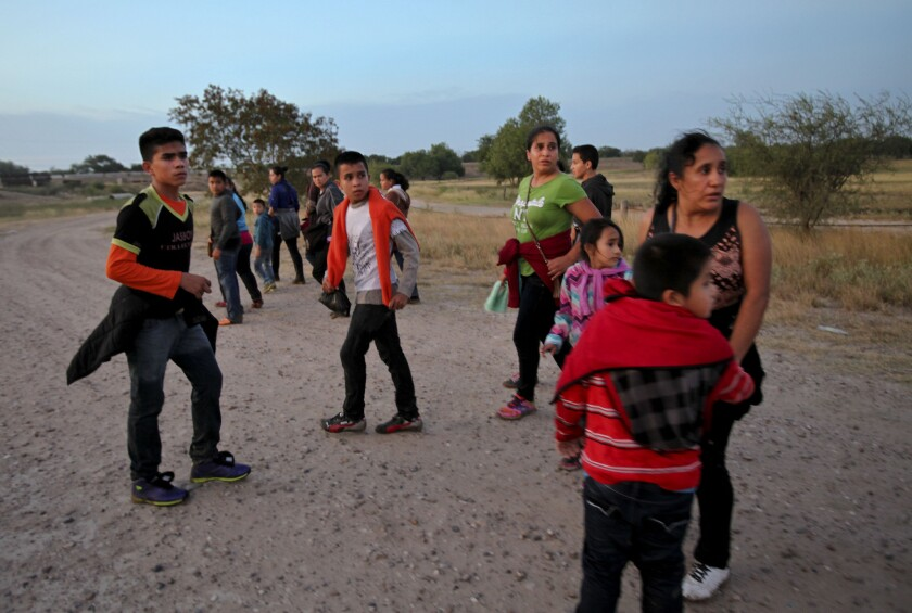 Migrants from Guatemala turn to face a local law enforcement official, not shown, giving them instructions after they crossed the Rio Grande near McAllen, Texas, in 2014.