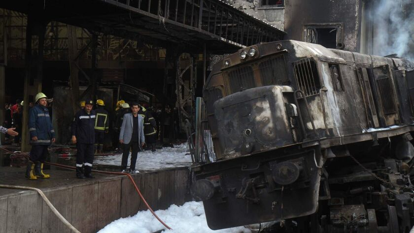 Firefighters and onlookers gather at the scene of a fiery train crash at Cairo's main railway station on Wednesday. More than two dozen people were killed.