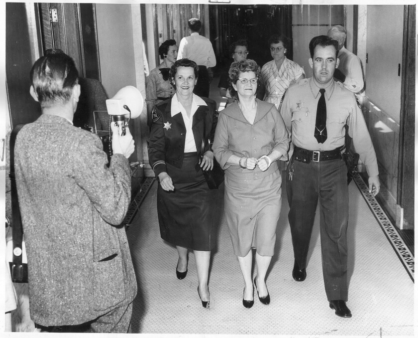 A March 17, 1959 file photo of Elizabeth Ann Duncan accompanied by Dep. Jeff Boyd, wearing a faint smile as she goes back to her cell to await the verdict to the jury.