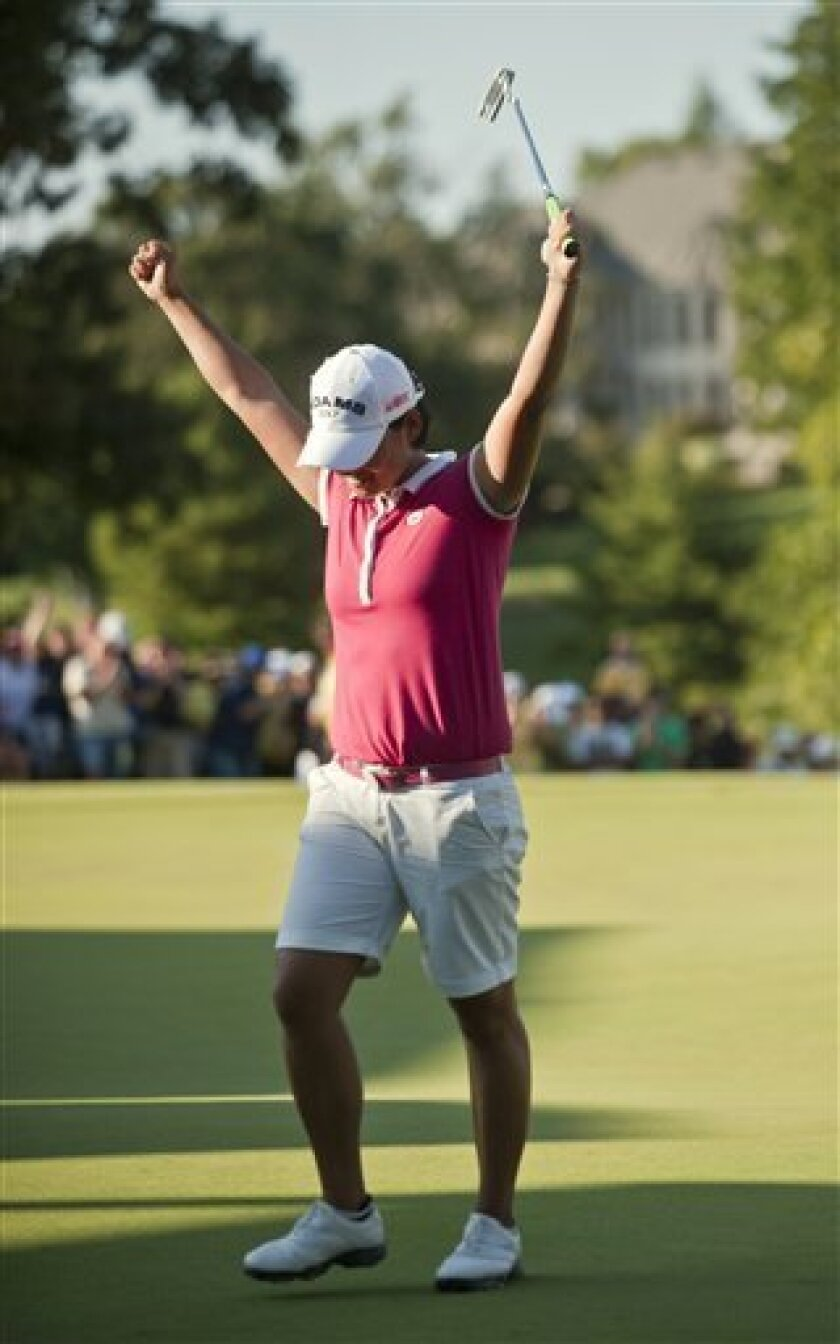 Yani Tseng, of Taiwan, reacts to sinking a putt during a playoff against Amy Yang to win the LPGA NW Arkansas Championship golf tournament Sunday, Sept. 11, 2011, in Rogers, Ark. (AP Photo/Beth Hall)