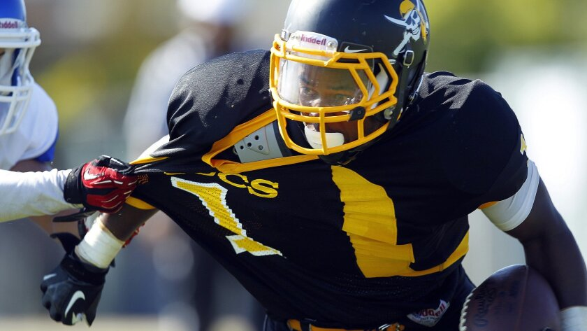 Mission Bay's Devante Kinder, who rushed for 109 yards on 16 carries, has his jersey pulled by an Orange Glen defender.
