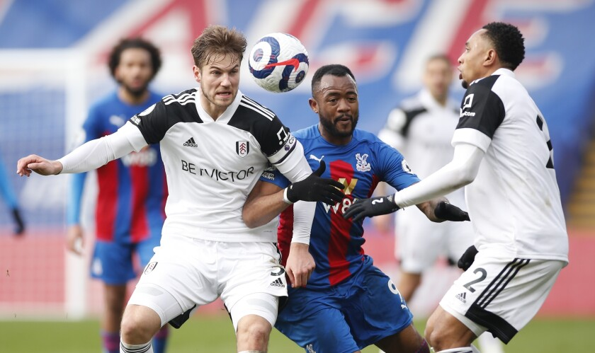 Crystal Palace's Jordan Ayew, center, vies with Fulham's Joachim Andersen, left, and Fulham's Kenny Tete during the English Premier League soccer match between Crystal Palace and Fulham at Selhurst Park stadium in London, England Sunday, Feb.28, 2021. (Andrew Boyers/Pool via AP)
