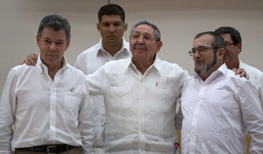 ARCHIVO - En esta fotografía del 23 de septiembre de 2015 el presidente de Cuba Raúl Castro, en el centro, abraza al mandatario de Colombia Juan Manuel Santos, a la izquierda, y al comandante de las Fuerzas Armadas Revolucionarias de Colombia (FARC) Timoleón Jiménez en La Habana. Santos dijo el miércoles 24 de agosto de 2016 que espera dar al país una noticia histórica relacionada con el cierre exitoso de las negociaciones de paz con las FARC. (AP Foto/Desmond Boylan, archivo)