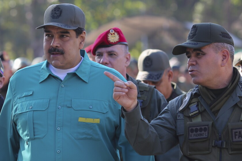 Handout picture released by the Venezuelan presidency showing Venezuela's President Nicolas Maduro (L) listening to Defence Minister Vladimir Padrino during military exercises at Fort Paramacay in Naguanagua, Carabobo State, Venezuela, on January 27, 2019. - Maduro on Sunday rejected a European ultimatum that he call elections as opposition rival Juan Guaido stepped up appeals to the military to turn against the leftist government.