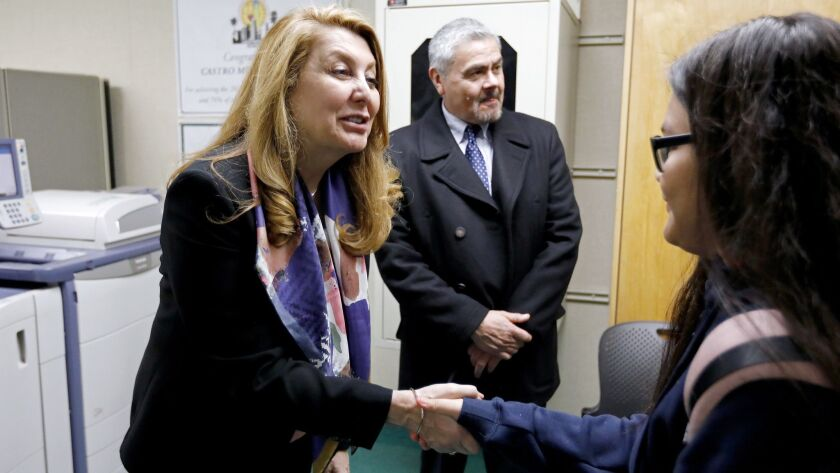 L.A. Unified Interim Supt. Vivian Ekchian, left, congratulates a student in January for winning a good attendance award. Ekchian has applied to remain in the top leadership job.
