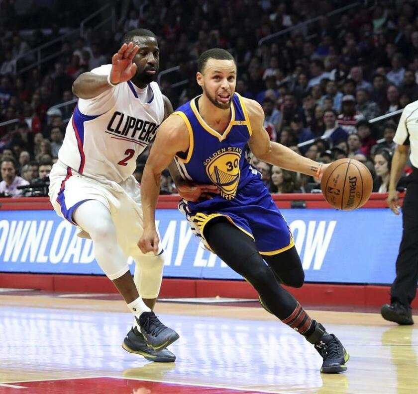 El jugador de los Warriors Stephen Curry (d) lucha por el balón con Raymond Felton (i) de los Clippers durante el partido de la NBA que enfrentó a los Golden State Warriors y a Los Angeles Clippers en el Staples Center en Los Ángeles, California. EFE