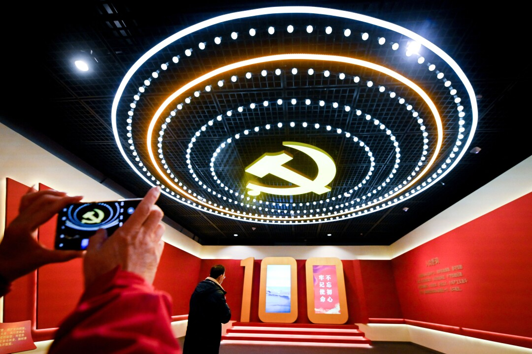 A hammer and sickle logo on the ceiling is ringed by lights in a red room