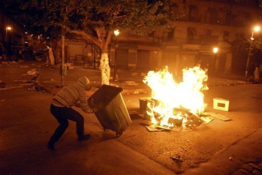 In this Thursday, Jan 6, 2011 picture made available Friday, Jan. 7, 2011 a youth pushes a garbage trolley into a fire in a street of the Bab el Oued district of Algiers, during the night as part of a protest over the rising cost of living. Violence came after price hikes for milk, sugar and flour in recent days, and amid simmering frustration that Algeria's abundant gas-and-oil resources have not translated into broader prosperity. (AP Photo)