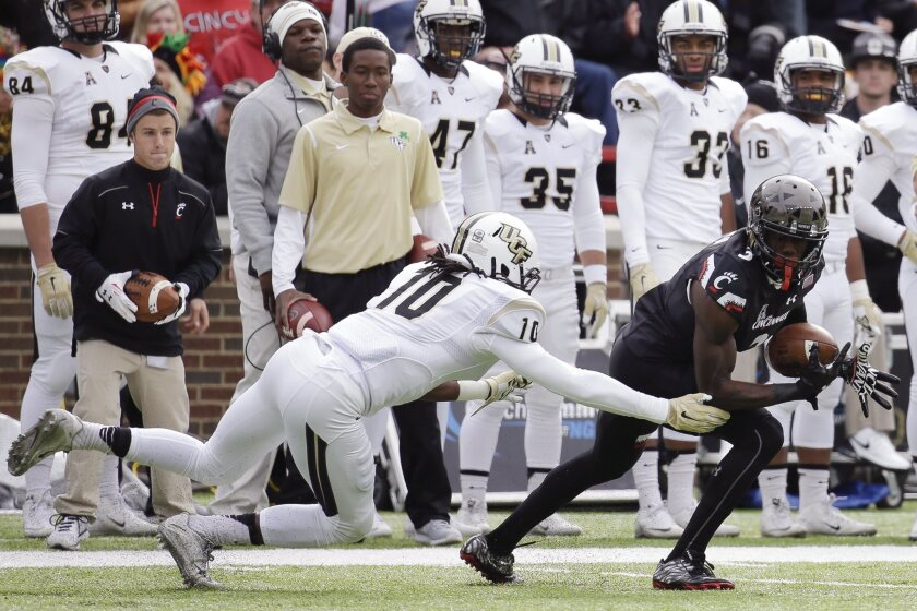 Cincinnati wide receiver Johnny Holton (3) catches a pass before breaking away from UCF defensive back Shaquill Griffin (10) for a touchdown run in the first half of an NCAA college football game, Saturday, Oct. 31, 2015, in Cincinnati. (AP Photo/John Minchillo)