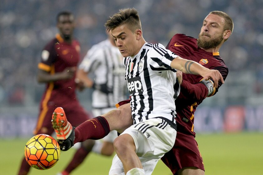 Juventus' Paulo Dybala, left, is challenged by Roma's Daniele De Rossi during a Serie A soccer match, at the Juventus stadium, in Turin, Italy, Sunday, Jan. 24, 2016. (AP Photo/Massimo Pinca)