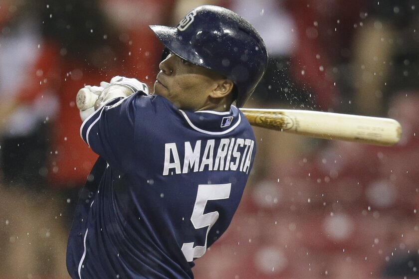 As rain falls, San Diego Padres' Alexi Amarista hits a double to deep left off Cincinnati Reds relief pitcher Burke Badenhop and drives home Cory Spangenberg in the sixth inning of a baseball game, Friday, June 5, 2015, in Cincinnati. (AP Photo/John Minchillo)