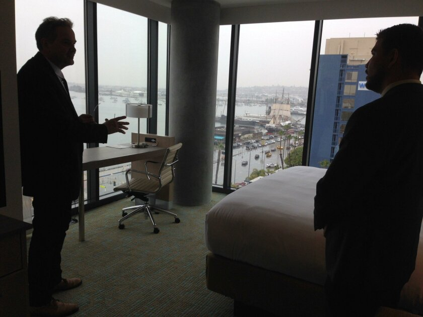 Architect Gordon Beckman and hotel sales executive Corey Lombard discuss the floor-to-ceiling windows as attractive to guests because of their expansive views.