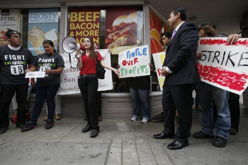 Wendy's employee Debra Flores spoke about her need to feed her two-year-old while balancing two different minimum wage jobs. At right is city councilman David Alvarez.