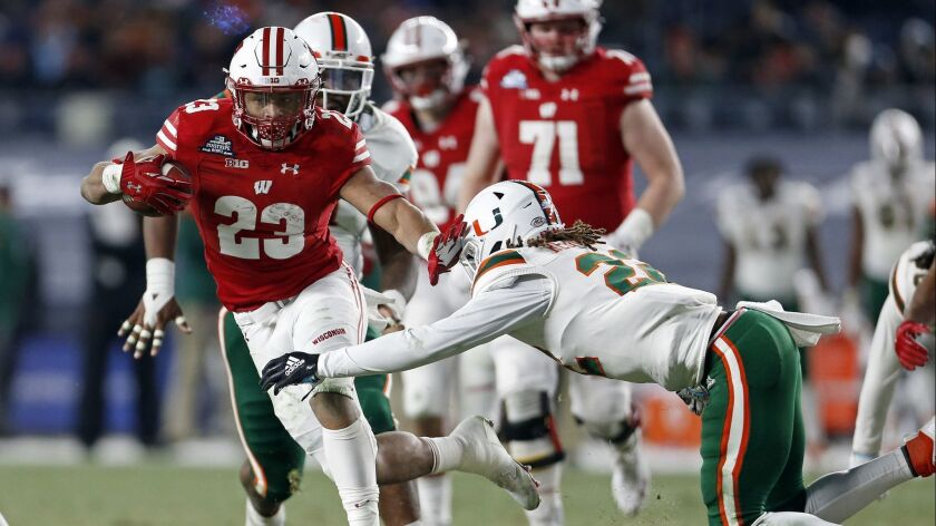 Wisconsin running back Jonathan Taylor (23) breaks a tackle attempt by Miami defensive back Sheldrick Redwine (22) during the first half of the Pinstripe Bowl.