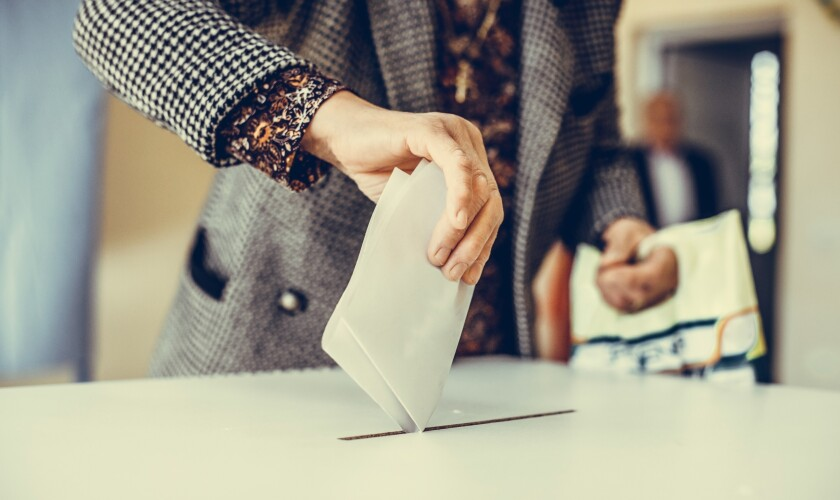 Person casting a ballot at a polling station