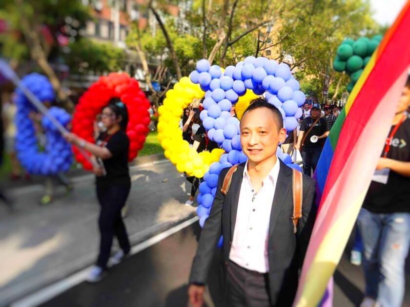 Chi Ta-Wei walks holding a flay with with other people holding ballons