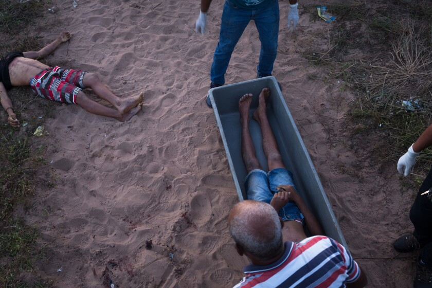Police officers examine body of man murdered in a row between the criminal factions PCC and Crime Syndicate in the city of Natal, Brazil.