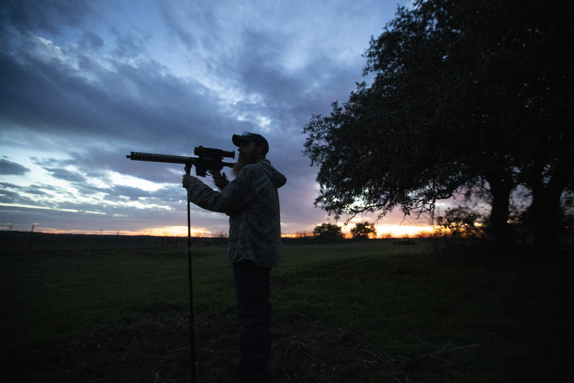 Fred Jones peers through the infrared scope on his rifle in rural Throckmorton County, Texas.