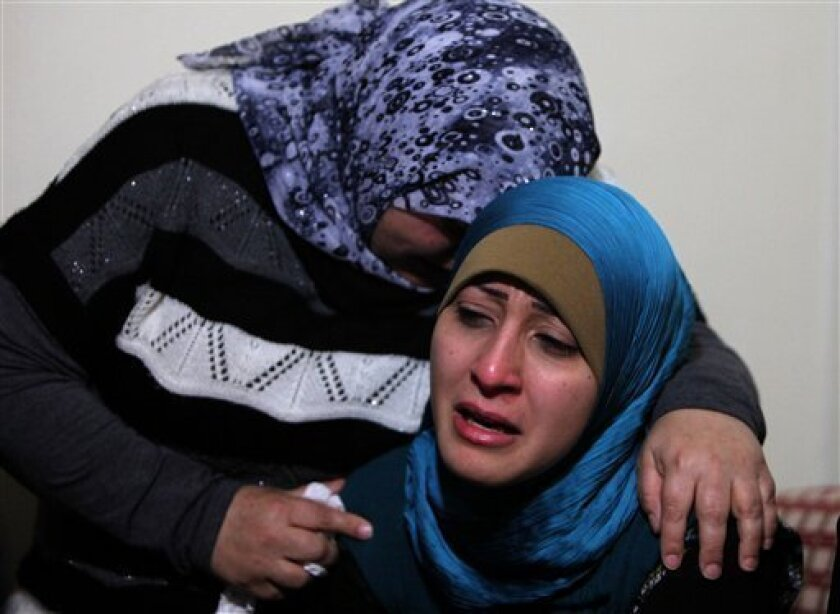 The sister, right, and an unidentified relative mourn for Ali Shaaban, a television cameraman working for Al-Jadeed TV who was shot dead on the Lebanon-Syria border, at their home in Beirut, Lebanon, Monday, April 9, 2012. Shaaban was killed when the channel's film crew came under fire in the border area of Wadi Khaled, the channel's head of news said. (AP Photo/Bilal Hussein)
