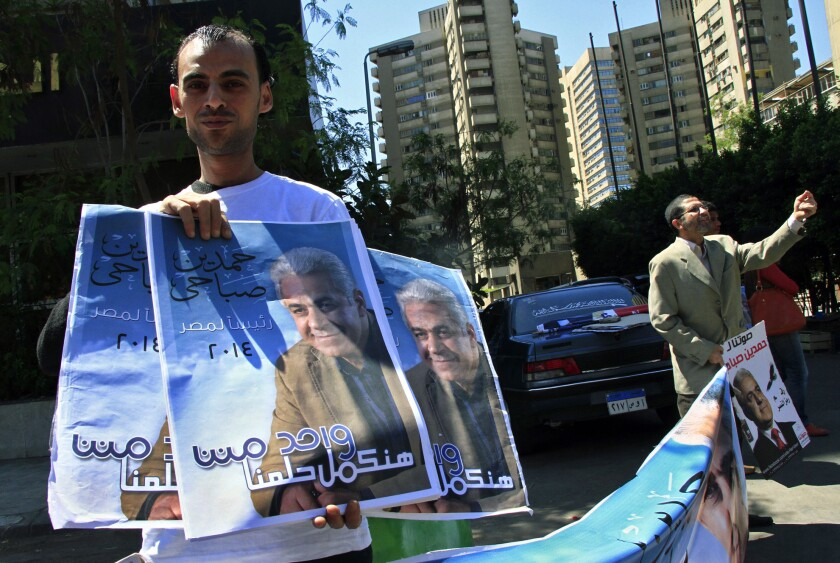 Supporters of leftist Egyptian presidential hopeful Hamdeen Sabahi hold posters of him on April 5 outside a Cairo office where citizens can authorize signatures for the nomination process.