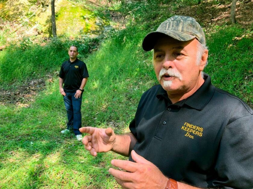 In this Sept. 20 photo, Dennis Parada (r.) and his son Kem Parada stand at the site of the FBI's dig for Civil War-era gold in Dents Run, Pa. The FBI says the excavation came up empty, but the Paradas believe investigators might have found the legendary gold cache.