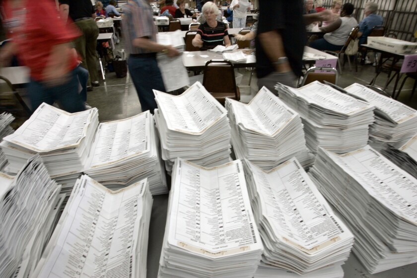 Workers at the registrar of voters office in Santa Ana open absentee ballots.