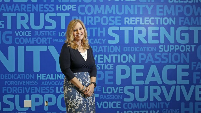 Founder Patricia Wenskunas poses for a portrait in front of a wall decorated with positive words at Crime Survivors in Santa Ana. Wenskunas started the nonprofit organization after suffering from a violent crime 16 years ago.
